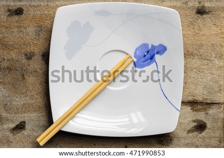Chopsticks and the beautiful white plate on the wooden.