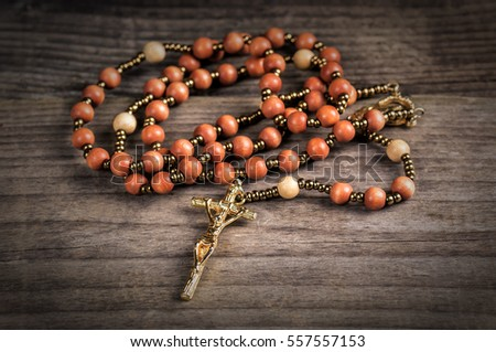 christian rosary on wooden background. Religion theme