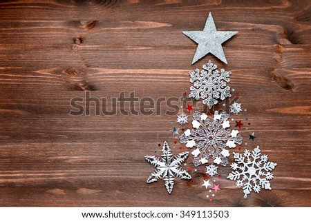 Christmas and New Year background with decorations in shape of fir-tree - balls, stars, silver sparkling snowflakes and confetti on wooden table. Place for text.