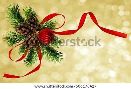 Christmas arrangement with pine twigs, cones and red silk ribbon bow on holiday background
