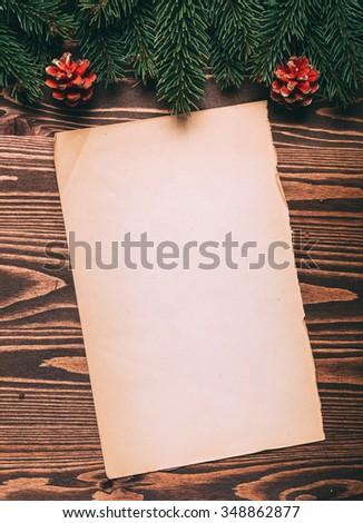 Christmas background, old blank vintage paper sheet with fir tree branches, around on a dark wooden background. Toned photo.