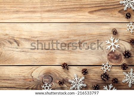 Christmas background with snowflakes and cones on wooden table with copy space. Top view