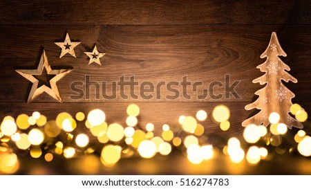 Christmas background with wooden ornaments arranged on a dark wood board and bokeh lights shining in the foreground
