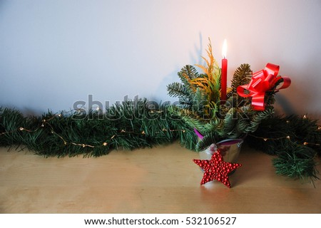Christmas candle ornament in a tin pot with evergreen branches and white lights on wood texture surface and white background