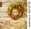 Christmas card design featuring  a home made christmas wreath with natural decorations hanging on a rustic wooden wall with text