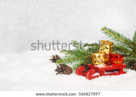 Christmas card with gifts on sledge standing on snow with fir branches