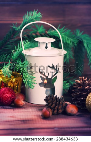 Christmas card with lantern, candle, fir tree, x-mas decorations, nuts and cones. Toned image, selective focus