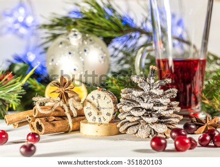 Christmas composition with candle, cinnamon, mulled wine and fir-cone on wooden background/ Christmas card with christmas rustic decorations