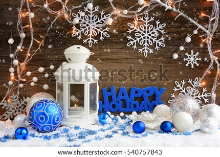"Christmas composition with lantern and the inscription ""Happy Holidays"" on wooden background"