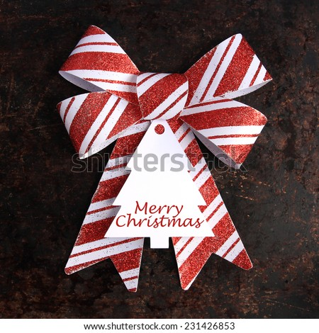 "Christmas concept. Red and white bow with ""Merry Christmas"" tag on brown rustic background."