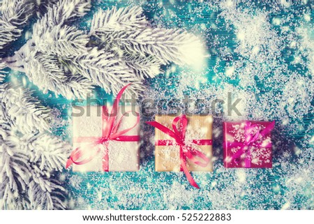 Christmas concept with gift boxes over snowbound wooden background
