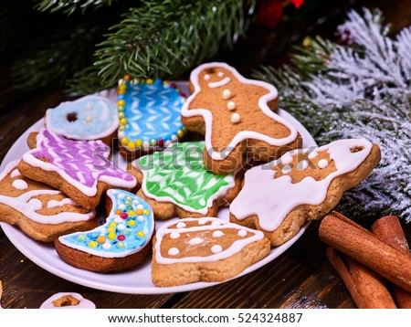 Christmas cookies on plate with fir branches. Christmas still life and cinnamon sticks.