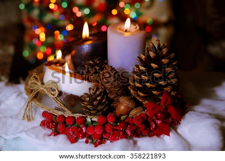 Christmas decoration closeup. Candles, fir cones. Eco still life. In the background are lit Christmas lights