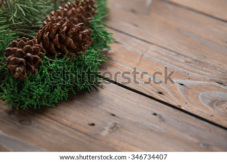 Christmas decoration: pine flowers cone and leaves on rustic brown wooden background