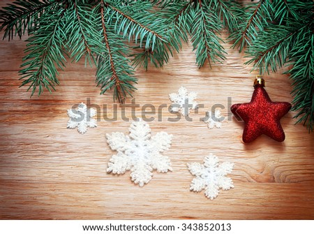 Christmas decoration. Snowflakes, red star and fir on a wooden background.