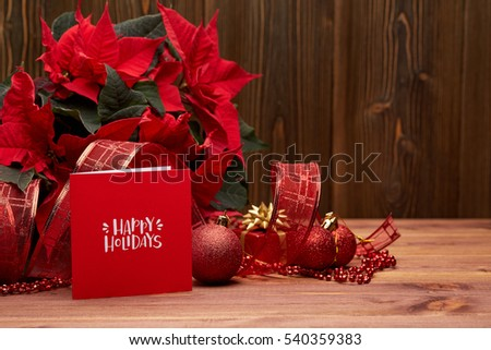 Christmas decoration with Red Poinsettia flowers (Euphorbia Pulcherrima), fir branch and mug with cocoa and marshmallows on wooden background.  New year and Christmas background with copy space.