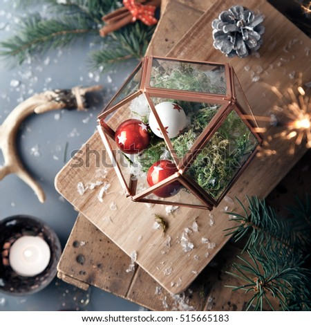 Christmas decorations: red and white baubles in glass terrarium, antlers, candles set on rustic wooden background