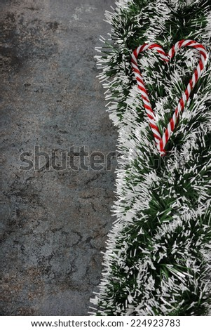 Christmas decorations - spruce tinsel and candy canes over dark background