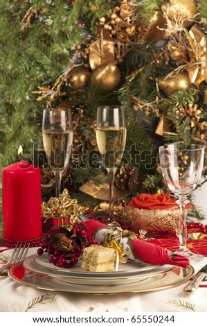 Christmas dinner place setting with Christmas table cloth,, plates, knife and fork, small presents, candles, christmas decorations champagne and wine glass, party