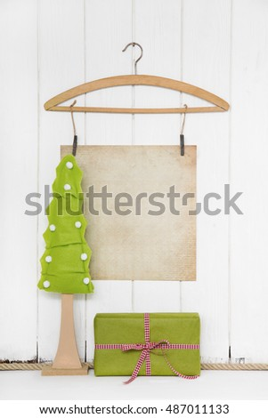 Christmas empty wooden background with a tree and a sheet of paper and a red green gift for coupon certificate in mock up style.