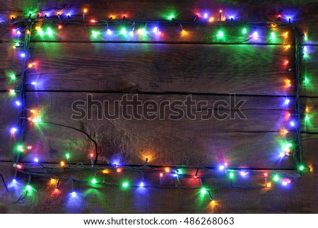 Christmas garland with colored paws on a dark wooden background.