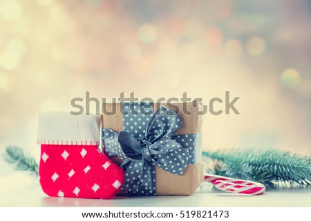 Christmas gift box and little sock with pine branch on background