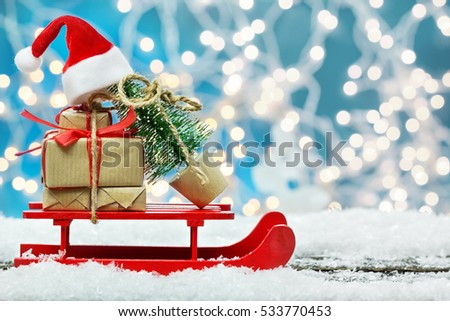 Christmas gifts and Fir tree with Christmas hat on sledge