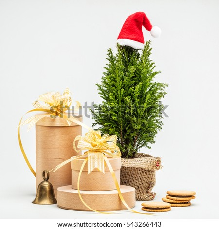 Christmas gifts in wooden boxes, Christmas tree in a pot, bell and cookies