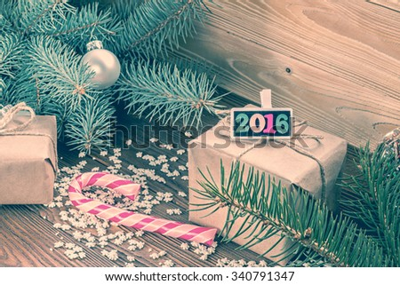 christmas gifts packaged in craft paper and black nameplate with colorful wood new year numbers, pink candy cane,  sprinkling as snowflakes on wooden table. Christmas tree with silver balls.