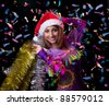 Christmas girl over tinsel and confetti on black background - stock photo
