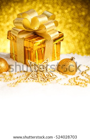 Christmas gold gift box with balls and decoration on snow. Studio shot