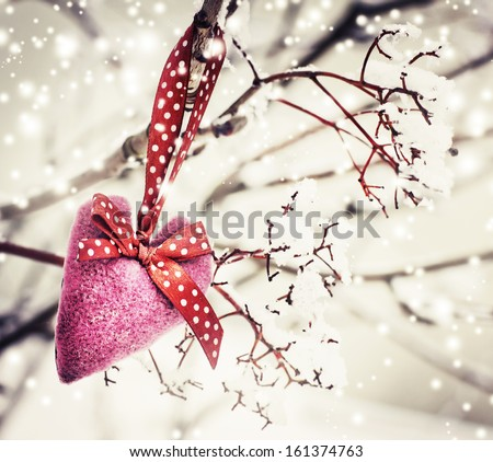 ... heart decoration with snow on winter nature background - stock photo
