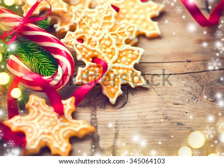 Christmas Holiday background with Gingerbread Cookies, Candy Cane and evergreens border over wooden table. Christmas and  New Year food