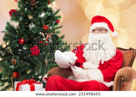 christmas, holidays and people concept - man in costume of santa claus with notepad, pen and christmas tree over beige lights background