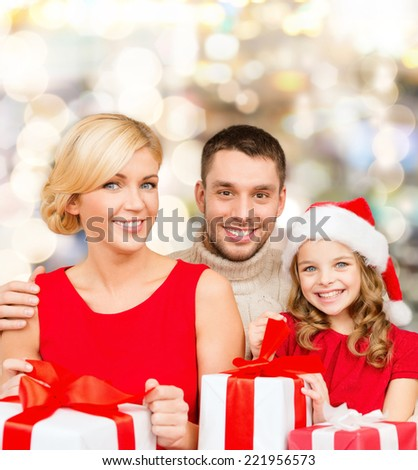 christmas, holidays,  family and people concept - happy mother, father and little girl in santa helper hat with gift boxes over lights background