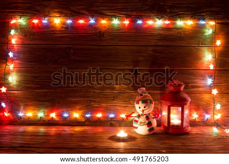 Christmas lights and vintage lantern and snowman on wooden background. Frame of lights. Merry Christmas. Christmas. Happy Christmas. Christmas background. Christmas light.