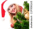 Christmas santa girl face behind a decorated fir-tree. - stock photo