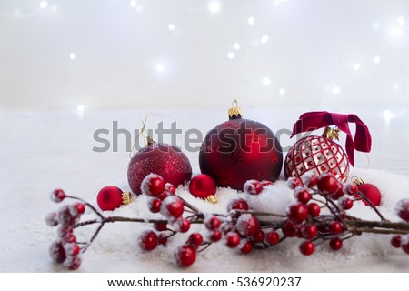 Christmas scene with snow - white and red balls with berries and lights in background