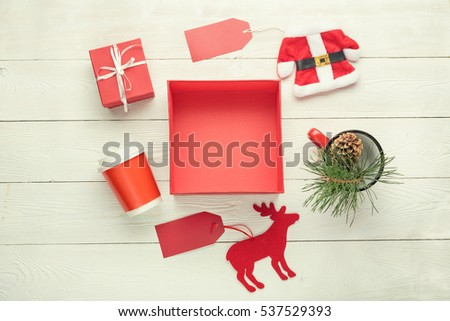 Christmas shopping concept. Empty red box, gift box, cup, santa costume with with price tag, deer toy with price tag, mug with green twig decor on white wooden background. Flat lay.