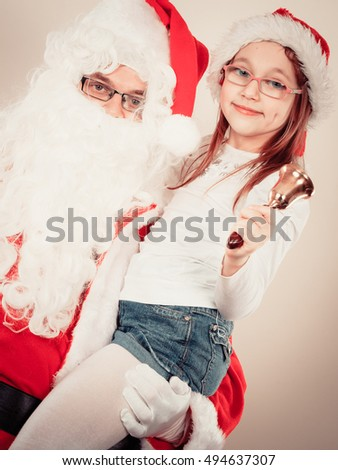 Christmas time people concept. Santa claus with little girl. Man has red outfit and child is hugging him. Shot taken at studio.