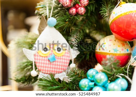 christmas Toy hanging on branch Burning Candles, Boxes, Balls, Pine Cones, Walnuts, Branchesin the background other decorations and garlands. copy space.