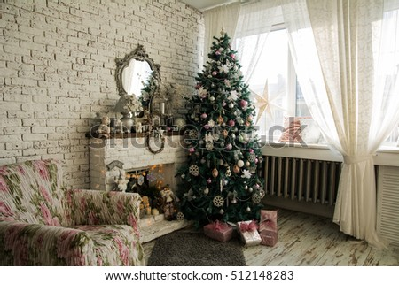 Christmas tree and fireplace with an armchair. Mirror on the brick wall background. Window curtains