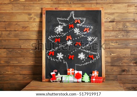 Christmas tree drawn on board and decorated with bows and snowflakes, on wooden background