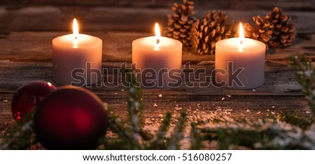Christmas winter candlelight with glowing candles, tree bulb, fir and tree cones on old wooden background, dark toned image in genuine style
