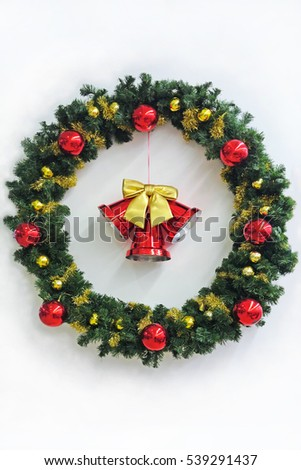 Christmas wreath and bell on a white wall