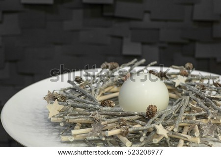 Christmas wreath of twigs and spherical candle decorated on a white plate on a dark background with tiles