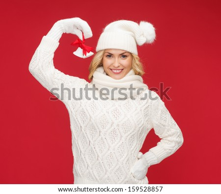 christmas, x-mas, winter, happiness concept - smiling woman in mittens and hat with jingle bells