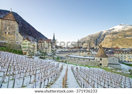 CHUR, SWITZERLAND - JANUARY 5, 2015: St Martin Church and vineyard of Chur at sunrise. Chur is the capital of canton Graubunden in Switzerland.