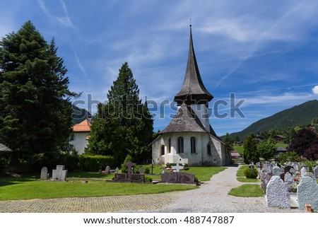Church with wooden roof  and cemetery in Rougemont Vaud canton of Switzerland