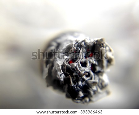 Cigarette or joint ash and ember, death skull face with eyes